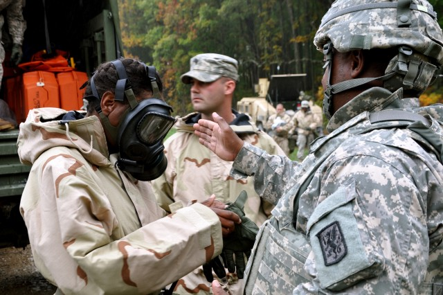 Sgt. 1st Class Quincy Suber, the chemical, biological, radiological, and nuclear platoon sergeant, gives Staff Sgt. Marshel Webb, an nuclear, biological, chemical squad leader, directions as she prepares to inspect the village for anything that might cause the villagers symptoms.