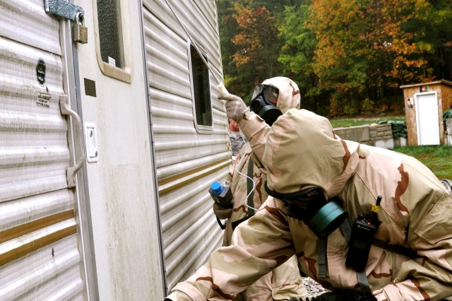 Nuclear, biological, chemical specialists Sgt. Michael Poindexter, from Dillion, S.C., and Spc. Matthew Saupe, from Seattle, Wash., inspect a trailer for hazardous material residue while searching a village for anything that would cause the villagers symptoms of nausea, vomiting, skin rashes.