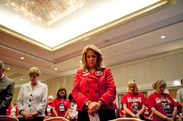 Tragedy Assistance Program for Survivors founder and military widow Bonnie Carroll pauses to remember all our fallen military, including,her husband, Brig. Gen. Tom Carroll, during the TAPS National Military Survivor Seminar in Arlington, Va. Others with her grieve for their fallen service members.