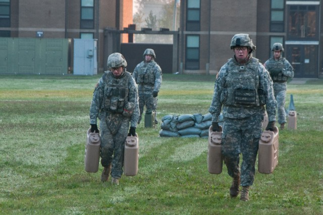 "FORT CAMPBELL, KY "" Spc. Michael Burghardt and Staff Sgt. Jason Lines of Headquarters and Headquarters Company, 2nd Brigade Combat Team, 101st Airborne Division (Air Assault), carry full 5 gallon water jugs for 300-meters, Oct. 4 at Fort Campbell's Strike Field during the Strike Brigade's combat focused physical training competition called the Iron Strike Challenge. The challenge is designed to push participants to their physical limits while promoting team and unit cohesion. (U.S. Army photo by Sgt. Mike Monroe, 2nd BCT PAO, 101st Abn. Div.)"
