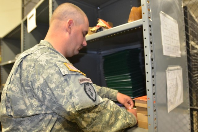 Spc. Thomas Moreland inventories supplies in the C Battery, 4th Battalion, 3rd Air Defense Artillery, supply room in preparation for his deployment. The Soldier recently won the Forces Command Supply Excellence Award.