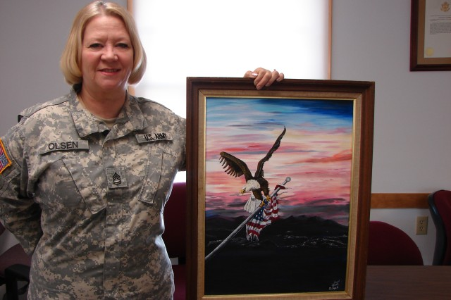 "Sgt. 1st Class Cheryl Olsen, a Soldier with the 2nd Battalion (Logistics Support), 411th Regiment of the 181st Infantry Brigade, stands next to her painting entitled ""Saving Our Ensign."" Olsen's effort earned her second place in the Novice Painting category of the 2012 Army Arts and Crafts Contest."