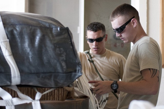 "Sgt. Jack Arnold (right), a resident of Macon, Ga., and Sgt. Craig Patrick (left), a resident of Kennesaw, Ga., both member of the 412st Quartermaster Company rigger detachment, inspect the webbing on a bundle being prepared for aerial delivery, Sept. 29. ""The Soldiers are constantly working,"" said Sgt. 1st Class Richard Davis, a resident of Water Rapids, Ga. and the non-commissioned officer in charge of the 421st rigger detachment. ""The Soldiers work long hours but they enjoy it. They don't fuss, we are down here to do one thing, put stuff down range, and we are not going to miss any mission at all."" (U.S.Army Photo by Army Staff Sgt. Peter J. Berardi, 316th Sustainment Command (Expeditionary))"