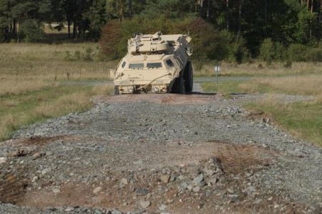 Sgt. John Rowland of the 615th Military Police Company navigates his M11-17 Armored Security Vehicle through one of the eleven obstacles of the new driver's training complex at the Grafenwoehr Training Area in Germany.