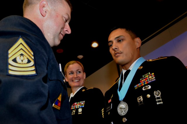 Command Sgt. Maj. James Wills, senior enlisted leader, 80th Training Command (TASS), congratulates Sgt. 1st Class Martin Rodriguez, acting first sergeant of the 1/104th Military Police Company following Rodriguez's induction into the Sergeant Audie Murphy Club while Sgt. 1st Class Jennifer Reisert, executive noncommissioned officer to the Army Reserve's command sergeant major looks on during the USARC SAMC induction ceremony hosted by the 80th Training Command (TASS) at Marshall Hall, Fort Knox Ky. Oct. 11, 2012.