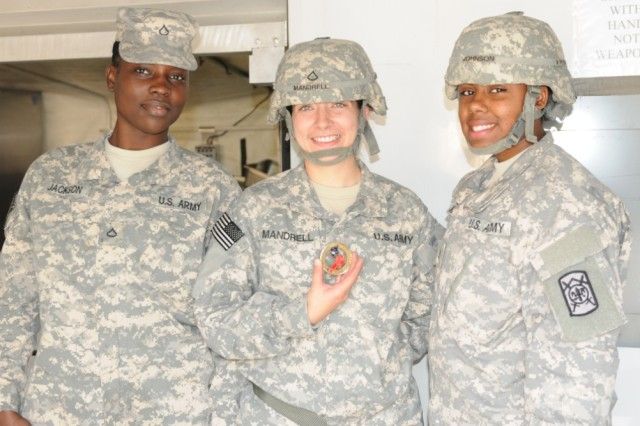 """CAMP CARROLL, South Korea"""" Army Pfc's Simone Jackson, Tara Mandrell, and Xaviera Johnson, Food service Specialists assigned to the 501st Sustainment Brigade display the 19th Expeditionary Sustainment Command coin of Excellence awarded by Brigadier General Paul C. Hurley, 19th ESC commander during Warpath II, at Camp Carroll, October 5, 2012. (U.S. photo by Army Staff Sgt. Robert DeDeaux 501st SBDE Public Affairs)"""