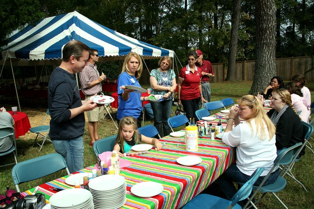Kerrie Branson, Survivor Outreach Services coordinator, center in blue, shows examples of plates painted as art therapy to survivors attending the U.S. Army Space and Missile Defense Command/Army Forces Strategic Command-sponsored SOS Fall Fest at the home of Lt. Gen. Richard P. Formica, SMDC commanding general, Oct. 13.