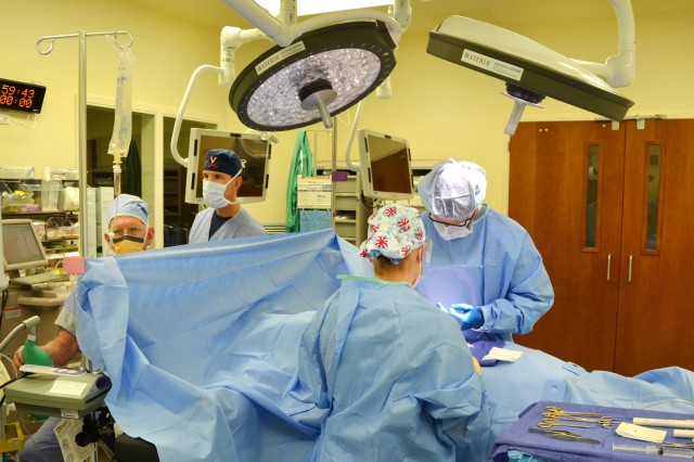 Nurse anesthesiologist Dan Barton (from left) and Lt. Col. Eric Lewis, chief of anesthesia and perioperative services, monitor a patient's sedation while Spc. Mikayla Cornfield, operating room technician, assists general surgeon Dr. Todd Lucas during same-day surgery at U.S. Army Health Center Vicenza Oct. 2, 2012. The recent addition of operating room staff at the health center has expanded the range of same-day surgical services available to Soldiers and civilians, and reduced the need to travel off-post for medical treatment.