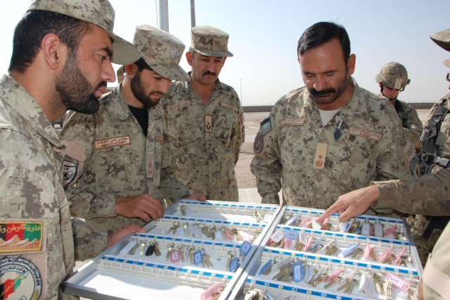 Afghan Civil Order Police led by Brig. Gen. Muhiuddin Sarwari take possession of a box of keys that fit the doors of their new facility near Kandahar City.