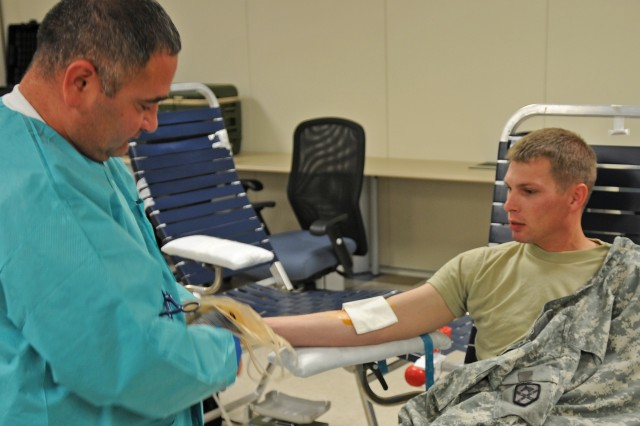 """FORT BLISS, Texas """" Jeff Rodriguez, medical technician at William Beaumont Army Medical Center, prepares Spc. Steven Kay, a supply specialist for 15th Sustainment Brigade, to donate blood Oct. 2, 2012. The 15th SB hosted the blood drive at its brigade headquarters on Fort Bliss, TX, to help increase the emergency blood supply used for Servicemembers in need. To continue these life-saving measures the 15th SB is scheduled to conduct additional   blood drives on Oct. 15 and 16 at its brigade headquarters. (U.S. Army photo by Sgt. Robert Golden, 16th Mobile Public Affairs Detachment)"""