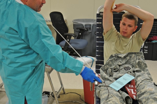 """FORT BLISS, Texas """" Spc. Steven Kay, a supply specialist in 15th Sustainment Brigade, watches as Jeff Rodriguez, medical technician at William Beaumont Army Medical Center, prepares his donated blood for packaging Oct. 2, 2012. Kay volunteered to donate blood at an Armed Services blood drive hosted by the 15th SB at its brigade headquarters on Fort Bliss, TX, to help increase the emergency blood supply used for Servicemembers in need. """"My blood could help save a battle buddy's life,"""" said Kay. To continue these life-saving measures the 15th SB is scheduled to conduct additional   blood drives on Oct. 15 and 16 at its brigade headquarters. (U.S. Army photo by Sgt. Robert Golden, 16th Mobile Public Affairs Detachment)"""
