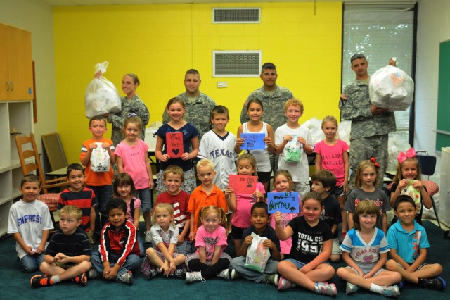 FORT HOOD, Texas--Students of Thomas Arnold Elementary School and Soldiers assigned to Headquarters and Headquarters Company, 4th Brigade Combat Team, 1st Cavalry Division, showcase some of the freedom bags given to the adopted unit Oct. 4 at the school, located in Salado, Texas. Each student in the school brought in goodies and decorated the bags to give to Soldiers for their upcoming deployment to Afghanistan and as a token of appreciation for all that the unit does.