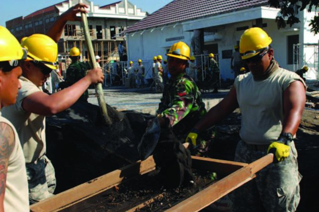 A Tentara National Indonesia Angkatan Darat soldier and U.S. Army Reserve soldiers of the 871st Engineer Company, based in Hilo, Hawaii, sift dirt for use in the construction of a community center in Malang, Indonesia. They participated in a combined exercise between the U.S. Army and TNI-AD that promotes cooperation between the two forces and improves peacekeeping and stability operations and the disaster relief capabilities of both armies.