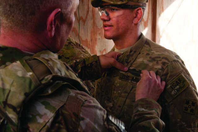 The 14th Sgt. Maj. of the Army, Raymond Chandler, pins the Combat Infantryman Badge on Pfc. Luis Uribarri at Combat Outpost Bari Alai, Afghanistan. Seven other members of the brigade also received combat badges from the sergeant major for their successful suppression of an insurgent attack on their outpost just days after arriving in Afghanistan.