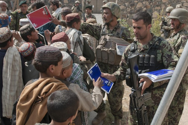 Afghan soldiers with the 5th Kandak, 3rd Brigade, 205th Corps, hand out school supplies to children at the Pir Mohamed School in Sanjeray, Afghanistan, Oct. 11, 2012.