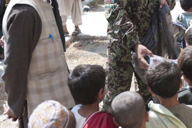 Lt. Col. Sher Ali, who serves as commander of the 5th Kandak, hands out school supplies to children at the Pir Mohamed School in Sanjeray, Afghanistan, Oct. 11, 2012.