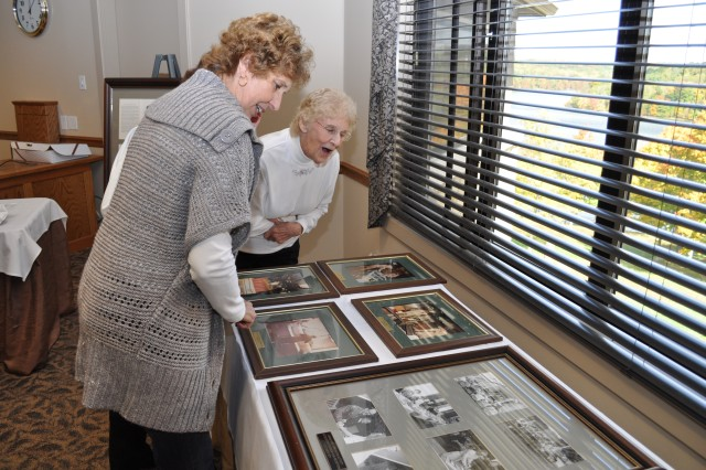 Former Crane Army Ammunition Activity employees Trudy Hammond (left) and Eve Chilton look at photos from CAAA's past during a Homecoming Luncheon. Crane Army Ammunition Activity celebrated its anniversary in October, marking 35 years since the U.S. Army activity was organized and given the responsibility of all conventional ammunition activity at then Naval Weapons Support Center, Crane.