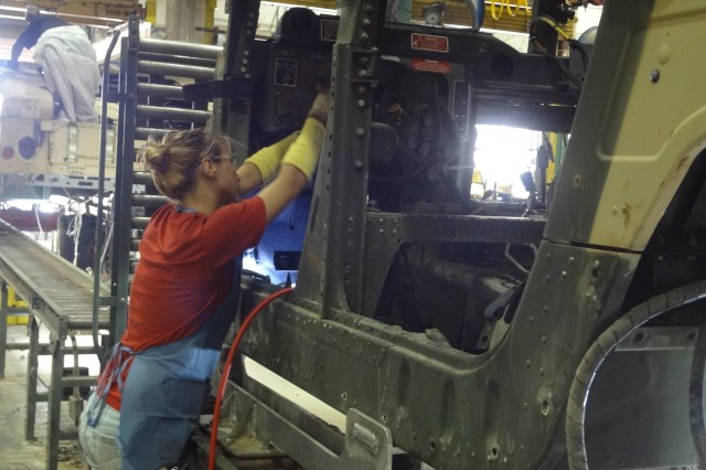 An employee of Red River Army Depot works to rebuild a High Mobility Multipurpose Wheeled Vehicle. RRAD is designated as the Secretary of the Army Center of Industrial and Technical Excellence for the Humvee as well as other tactical and combat vehicles.