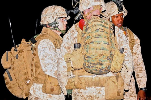 Three Marines from Marine Air Station Yuma discuss operation maneuvers during the training exercise at Fort Huachuca's Libby Airfield on Friday night.