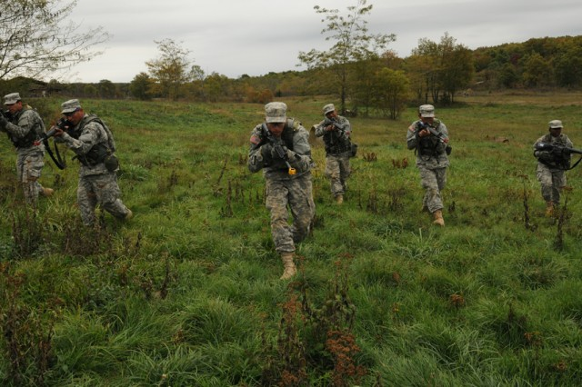 Soldiers from Co. C, 1-48th^Inf. Bn., move in a tactical formation across a field during the unit's final Field Training Exercise of Basic Combat Training.