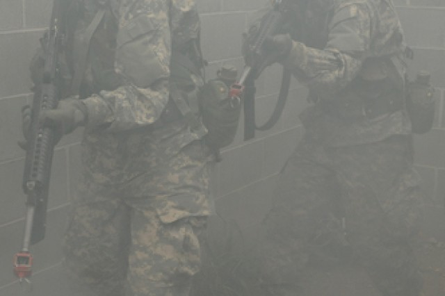 Soldiers move through smoke to clear a building during their final FTX of Basic Combat Training.