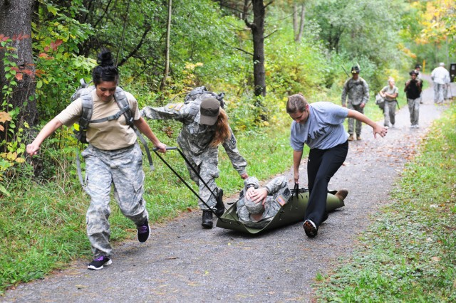 """Military spouses with 3rd Squadron, 71st Cavalry Regiment, 3rd Brigade Combat Team, evacuate a """"casualty"""" to a medical evacuation site as part of the """"Spouses Spur Ride"""" held recently by the squadron."""