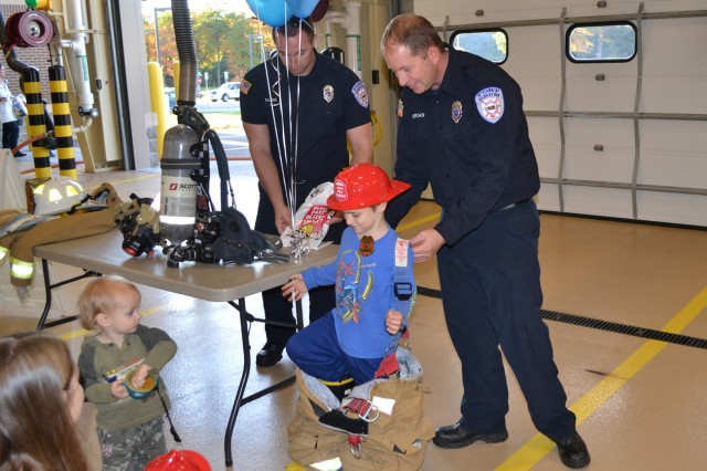 A future firefighter gets help dressing for the job during the Firefighter for a Day event Oct. 9.