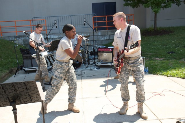 Staff Sgt. Linda Wolfe sings to her guitar player, Sgt. Aaron Szczepaniec, during a military appreciation event at Syracuse University.