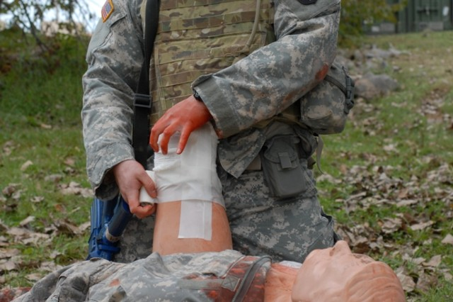 Specialist Elliot Cervera, a 25-year-old forward observer from Bridgeport, Conn. and in 1st Squadron, 33rd Cavalry Regiment, 3rd Brigade Combat Team, 101st Airborne Division applies gauze and tape over a wound on a simulated casualty near his headquarters building Oct. 11 while conducting the trauma lane portion of a combat life-saver class. This type of training teaches non-medical personnel to apply treatment to their battle buddies in combat situations when medics are not present, which greatly improves the chances of survival. (U.S. Army photo taken by Sgt. Alan Graziano, 3rd Brigade Combat Team, 101st Airborne Division)