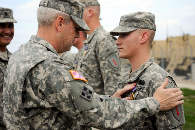 Brig. Gen. Donald MacWillie, senior commander, Fort Riley, pins a Purple Heart medal on Spc. Alec Moran, Troop A, 4th Sqdn., 4th Cav. Regt., at an Oct. 11 ceremony at Fort Riley. Moran was hit with shrapnel when his combat outpost was attacked with an 82mm recoilless rifle during the squadron's most recent deployment to Afghanistan. The troopers returned in February to Fort Riley.