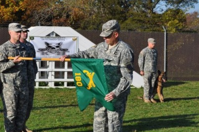 FORT LEONARD WOOD, Mo. -- Lt. Col. Jeffrey Bevington, 92nd Military Police Battalion commander, unfurls the colors of the 180th Military Working Dog Detachment during a ceremony October 16, 2012 recognizing the unit's activation. The 180th MWD Detachment is the first military police working dog detachment to be established on post.