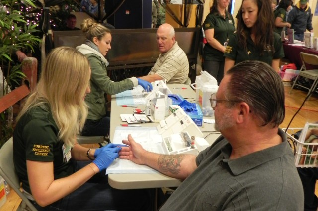 Julie Richards, left, from the Army Wellness Center, draws blood to test Air Force veteran Dennis Shultz's cholesterol.