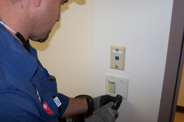 FORT CARSON, Colo. -- Johnnie Miranda, Fort Carson Support Services general maintenance worker, installs an occupancy sensor, which turns on lighting in the barracks.