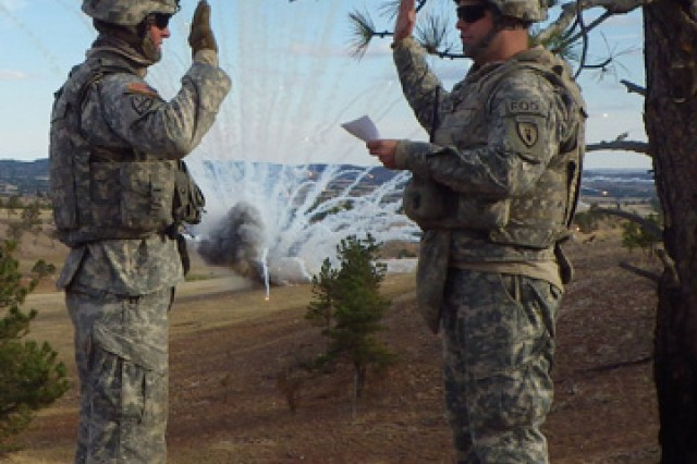 Capt. Clay Kirkpatrick, right, commander, 663rd Ordnance Company, 242nd Explosive Ordnance Disposal Battalion, 71st Ordnance Group (EOD), re-enlists Sgt. Christopher Chesla, 663rd Ord., as a 155-mm white phosphorus unexploded ordnance detonates.