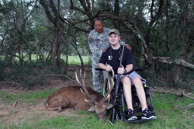 "FORT SAM HOUSTON, Texas - Spc. Michael Crawford, along with Maj. Gen. Adolph McQueen Jr., deputy commanding general for support, U.S. Army North, show off the  ""9-point"" Sika Deer that Crawford bagged Oct. 11 as part of a hunting trip for Wounded Warriors at a private central Texas game ranch. The Sika is a large, shaggy deer from eastern Asia. ""The atmosphere makes it fun,"" said Crawford, a 21-year-old military policeman who is confined to a wheel chair after an IED blast in Afghanistan. Crawford, a native of Vancouver, Wash., said he plans to eat the deer meat for Christmas dinner. (U.S. Army photo by Staff Sgt. Keith Anderson, Army North PAO)"