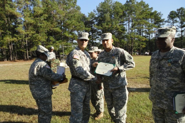 FORT JACKSON, S.C.--Maj. Gen. William Buckler, Jr., commander of 412th Theater Engineer Command, presents Spc. Abid Mughal, Human Intelligence Collector and resident of Columbia, S.C., with the Army Achievement Medal and Letter of Commendation from Army Gen. Cho of the Republic of Korea, for his support in Operation Key Resolve, Oct. 13, 2012.