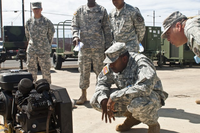 Sgt. Ulysses Fulton, motorpool sergeant for the 8th Special Troops Battalion, 8th Theater Sustainment Command, inspects the corrosion prevention equipment during corrosion prevention train-the-trainer training at the 8th STB's motorpool, Sept. 17.