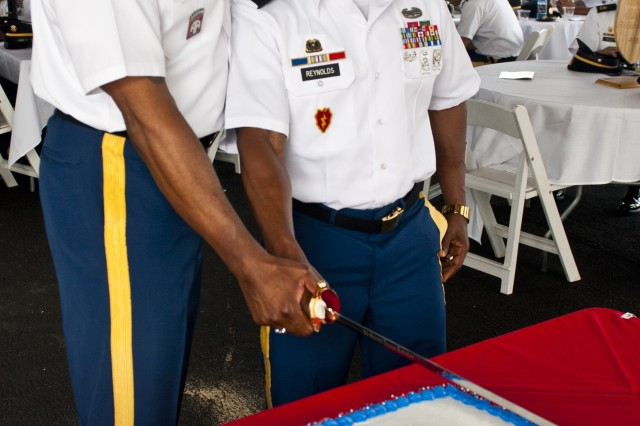 Command Sgt. Maj. Nathan Hunt, command sergeant major for the 8th Theater Sustainment Command, and the 8th TSC's oldest NCO, Sgt. Maj. Kenneth Reynolds, the current operations sergeant major for the 8th TSC, make the first cut into the ceremonious noncommissioned officer cake during the 8th TSC's NCO Call, Sept. 21, held at the USS Missouri.