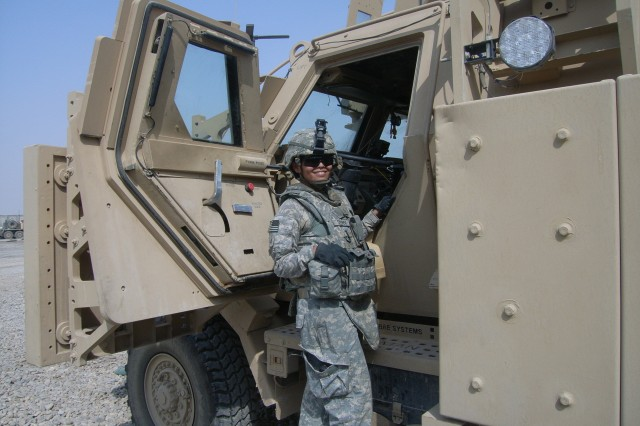 Pfc. Chelsea Draper, Forward Support Company, 1st Battalion, 8th Infantry Regiment, 3rd Advise and Assist Brigade, 4th Infantry Division, prepares to drive her military vehicle to its guard point protecting her base in Maysan, Iraq.