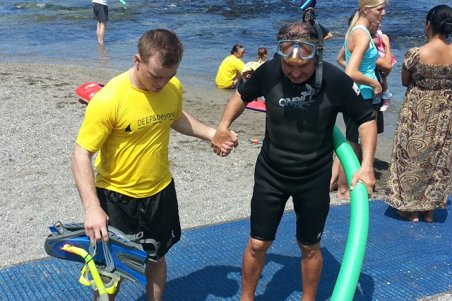 Spc. Peter Partridge, construction equipment mechanic for the 561st Engineer Battalion, 84th Engineer Battalion, 130th Engineer Brigade, 8th Theater Sustainment Command, helps his new friend, David, climb the stairs to rinse off after snorkeling during Deep & Beyond's Snorkel Day at Kahaluu Beach in Kona, Hawai'i, Sept. 21.