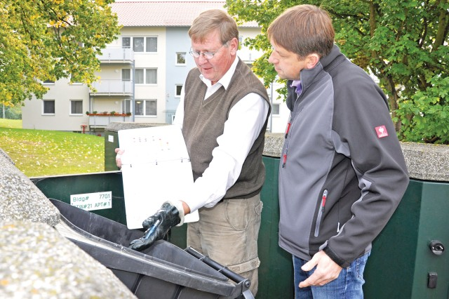 Marty Hanson (left), a Directorate of Public Works recycling contractor, and Peter Zeisberger, DPW solid waste manager, look into a trash can on Westfalen Strasse in Wiesbaden's Aukamm Housing in Germany.