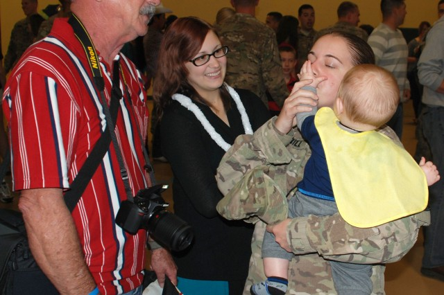 A corporal reunites with family members after her redeployment from Afghanistan with the 14th Military Intelligence Battalion. (U.S. Army photo by Gregory Ripps)