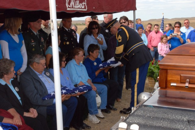 "Sgt. 1st Class Eric Christopherson, a member of the South Dakota Army National Guard Military Honors team, presents a folded American flag to Julie Marshall, the eldest surviving sister of Sgt. 1st Class Arthur F. ""Bluie"" Jewett, during a burial ceremony held near White Horse, S.D., Sept. 25. Jewett, a member of the Cheyenne River Sioux Tribe, was killed-in-action during the Korean War's Chosin Reservoir campaign."