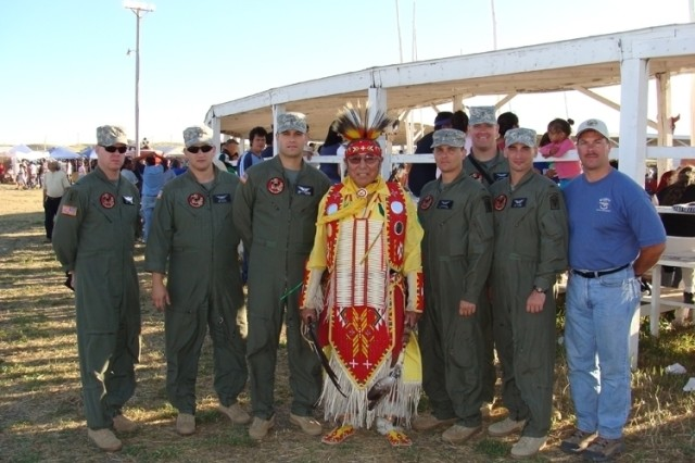 The crews of two Lakota helicopters from Fort PolkAca,!a,,cs 5th Aviation Battalion pose with a Lakota performer at the powwow in South Dakota.