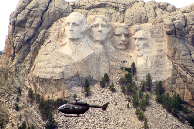 A UH-72 Lakota Light Utility Helicopter from Fort Polk, La., flies past Mount Rushmore on its way to the Lakota powwow in South Dakota.
