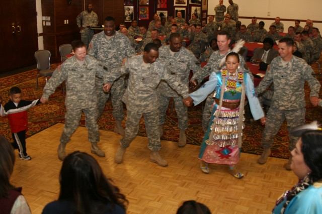 Members of the Seven Falls Indian Dancers and participants dance in a circle at the Elkhorn Conference Center Nov. 17 at Fort Carson, Colo.