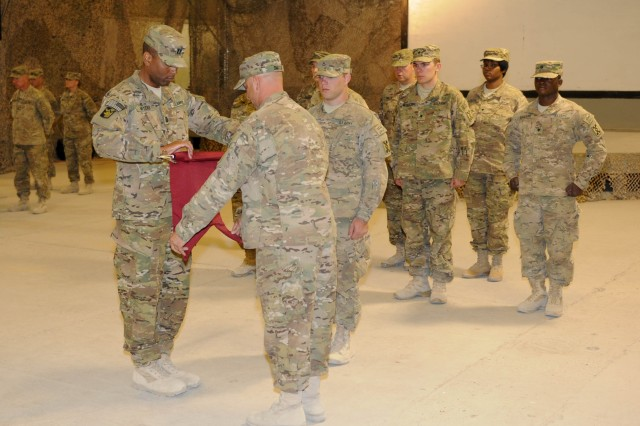 Capt. Ronald Myers, the commander of the 576th Movement Control Team, and Staff Sgt. James Smith, the 576th MCT's detachment sergeant, uncase their unit's colors during a transfer of authority ceremony on October 20, at Kandahar Airfield, Afghanistan. During the ceremony, the 822nd MCT, a U.S. Army Reserve unit from Boston, Mass., transferred its to the 576th MCT, an Army Reserve unit from Panama City, Fla. (U.S. Army photo by Staff Sgt. Michael Behlin)