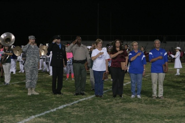 From left to right, Sgt. 1st Class Craig Hannum, 18th Military Police Detachment sergeant; Fry Firefighter Steve McMurtrie; Sgt. Ken Foster, Cochise County deputy sheriff, Shelby Weller, manager of Casa De La Paz, Hospice, Sierra Vista Regional Health Center; Shawnee Carlile, Family Readiness support assistant, 11th Signal Brigade and Margaret and Rick Klein, school community Buena Performing Arts Center managers, display their awards during Buena's pre-game show Friday night.