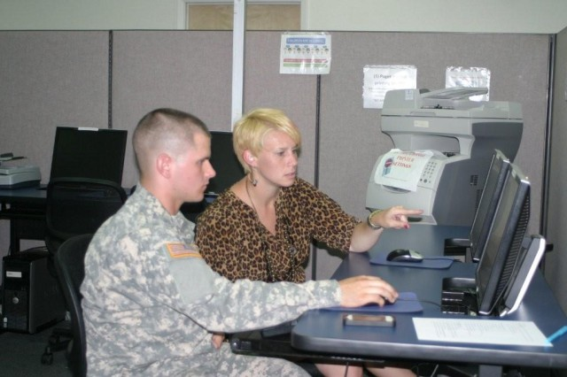 Education Services Specialist Erin Gibson assists Pfc. Orville Arel, Headquarters and Headquarters Company, 40th Theater Tactical Signal Brigade, with setting up tuition assistance online. The Education Center has specialists available to help during all open business hours.
