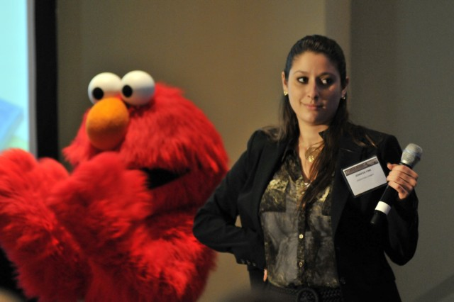 "Elmo and Jennifer Fink prepare to sing a song she co-authored titled ""The Little Champs"" at the end of the Family Forum IV, Oct. 24, 2012, at the 2012 Association of the United States Army Annual Meeting and Exposition.  Fink and her mother also co-authored a book titled ""The Little Champs,"" which is being released this week through USO."